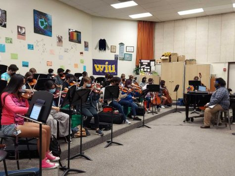 Chester leads the symphony orchestra during class.